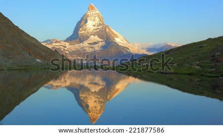 Matterhorn peak and peaceful reflection on Riffelsee at early morning - stock photo