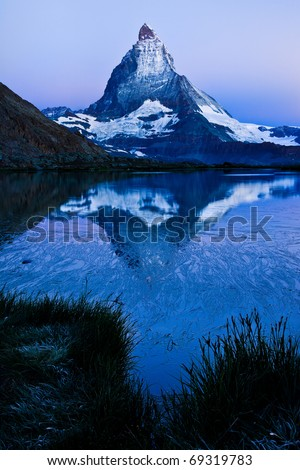 Matterhorn reflected in Riffelsee before dawn - stock photo