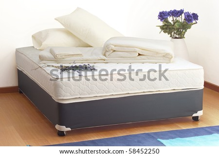 Mattress with sheets and pillows - stock photo