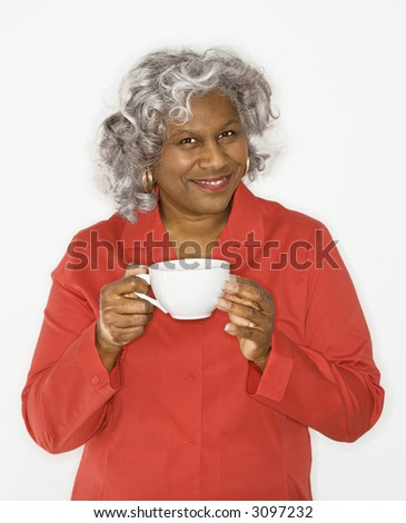 Mature adult African American female holding coffee cup smiling.
