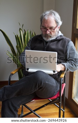 Mature Adult bearded working with laptop