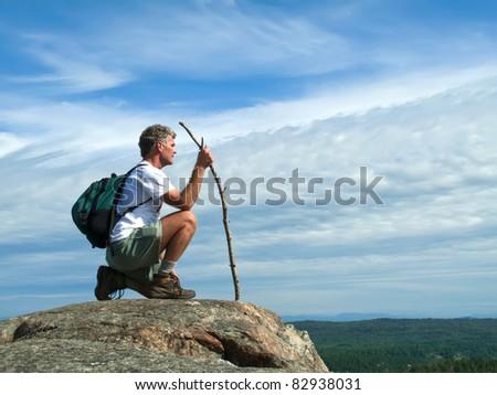 Mature Adult Caucasian Hiker Kneeling on Mountaintop - stock photo