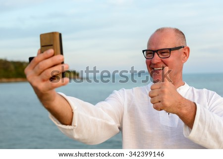 Mature adult man outdoors taking selfie picture with mobile phone and giving thumbs up - stock photo