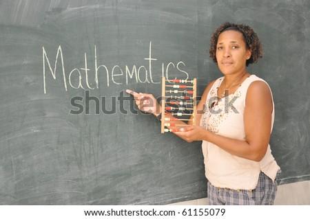 Mature African American Woman Teacher at Blackboard in Elementary School Classroom - stock photo