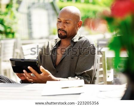 mature african man using smart phone outdoors - stock photo