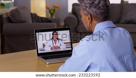 Mature African woman talking to doctor on laptop - stock photo