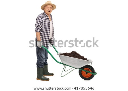 Mature agricultural worker pushing a wheelbarrow full of dirt isolated on white background - stock photo