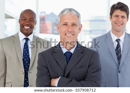 Mature and smiling director standing upright in front of his laughing executives - stock photo