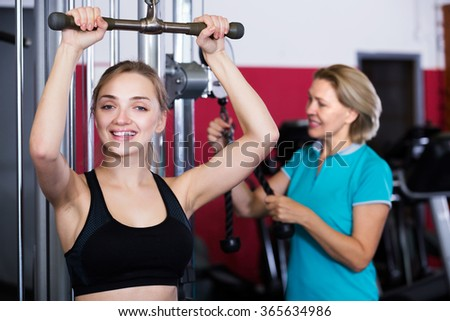 Mature and young women doing powerlifting on machines in jym