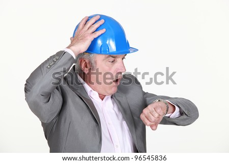 mature architect consulting his watch - stock photo