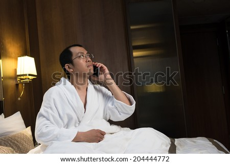 Mature Asian man in bathrobe in hotel, using cellphone. - stock photo