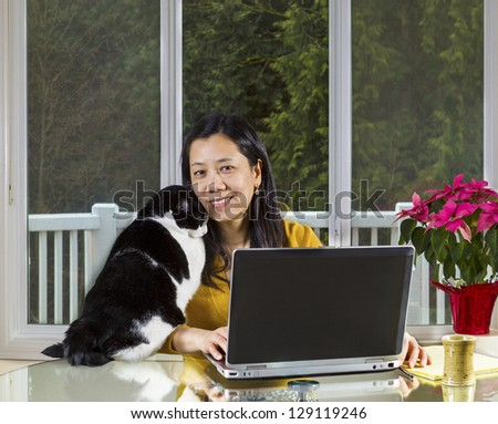 Mature Asian woman and family cat cuddling while working at home with large windows in background - stock photo