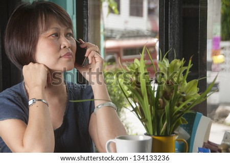 Mature Asian woman talking on telephone - stock photo