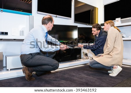 Mature assistant showing flat screen TV to couple in electronics section of hypermarket - stock photo