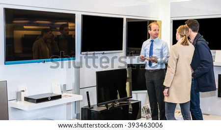 Mature assistant showing flat screen TV to young couple in electronics section of hypermarket - stock photo