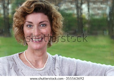 Mature attractive brunette woman on couch of her home - stock photo