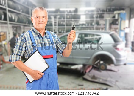 Mature auto mechanic with clipboard and car key in front of modern car during automobile maintenance at auto repair shop - stock photo
