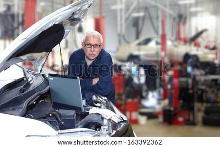 Mature auto mechanic working in car repair service. - stock photo