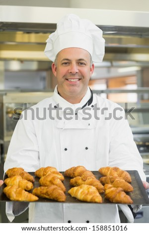 Mature baker presenting some croissants on a baking tray - stock photo
