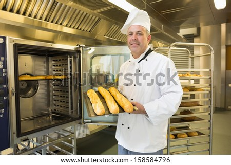 Mature baker showing three baguettes standing in front of an oven - stock photo