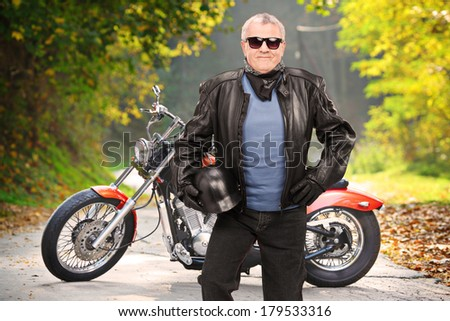 Mature biker in leather jacket standing in front of his chopper on an open road - stock photo
