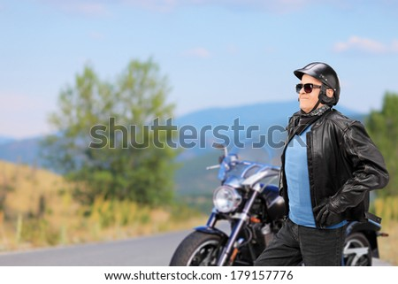 Mature biker walking in front of his motorbike on an open road - stock photo