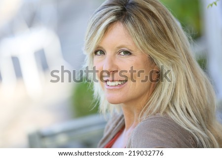 Mature blond woman relaxing in outdoor bench