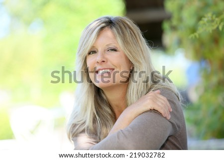 Mature blond woman relaxing in outdoor bench - stock photo