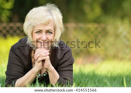 Mature, blonde woman in garden. - stock photo