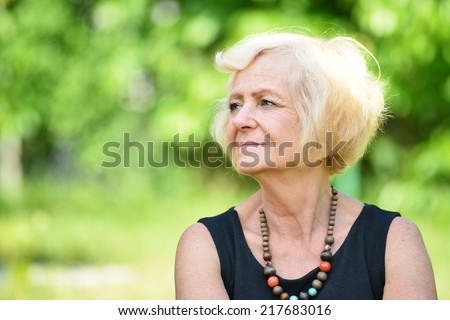 Mature, blonde woman in garden, MANY OTHER PHOTOS FROM THIS SERIES IN MY PORTFOLIO.  - stock photo