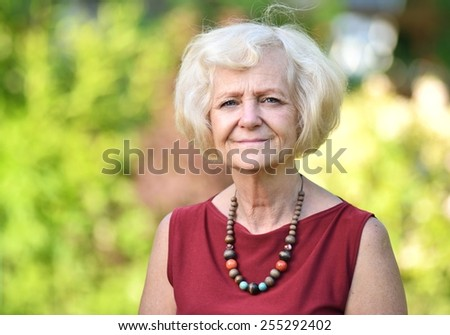 Mature, blonde woman in garden. MANY OTHER PHOTOS FROM THIS SERIES IN MY PORTFOLIO.  - stock photo
