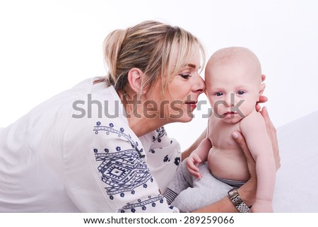 mature blonde woman playing and taking care of her lovely new born baby boy  - stock photo