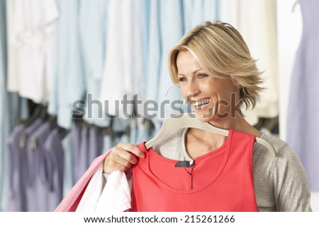 Mature blonde woman shopping in clothes shop, holding red vest top on coathanger, smiling - stock photo