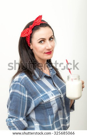 Mature brunette Caucasian woman wearing a blue flannel shirt and a red bow on her head is drinking a glass of milk with a white and red straw from a clear glass. - stock photo