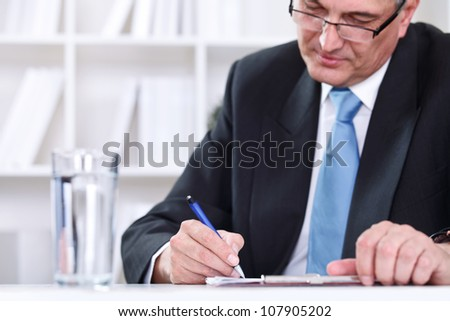 Mature business executive writing on papers at office desk - stock photo