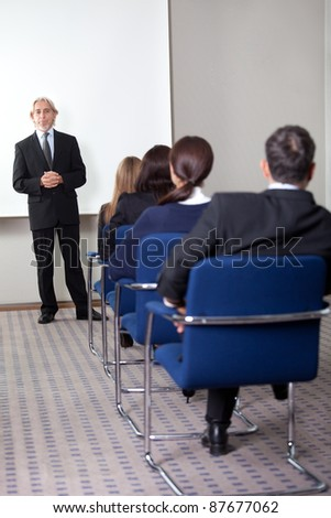Mature business man giving presentation to his colleagues at a meeting room - stock photo