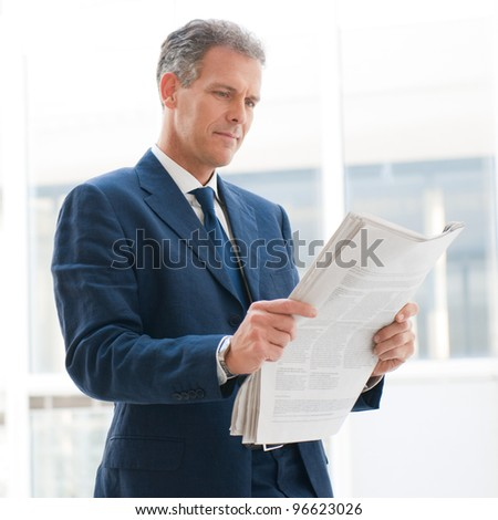 Mature business man reading news in the office - stock photo