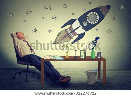 Mature business man relaxing at desk in his office. Happy senior businessman sitting on armchair daydreaming of corporate company prosperity. Future space tourism ambition concept  - stock photo