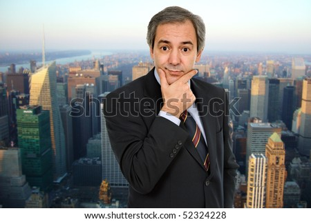 mature business man, thinking with his hand on the face - stock photo