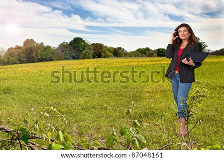 Mature business woman standing in field with cell phone and lap top computer. - stock photo