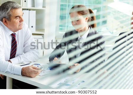 Mature businessman and his colleagues working at meeting in office - stock photo