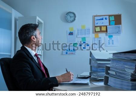Mature Businessman At Office Looking At Clock - stock photo