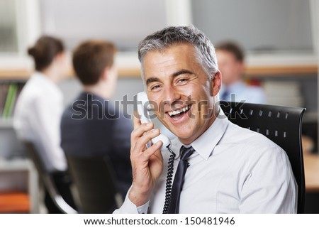 Mature businessman at the phone with colleagues in the background - stock photo