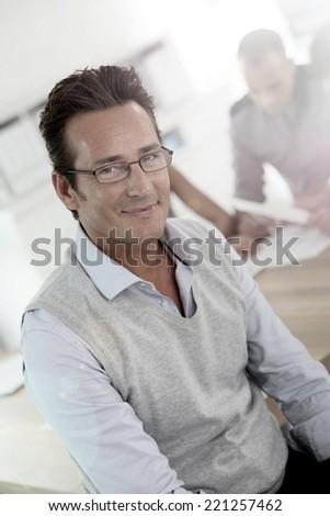 Mature businessman attending work meeting - stock photo