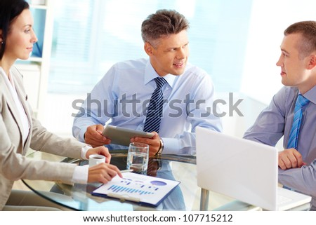 Mature businessman being satisfied with the ideas proposed by his colleagues - stock photo