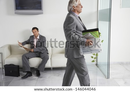 Mature businessman carrying box past a man reading newspaper in office hallway - stock photo