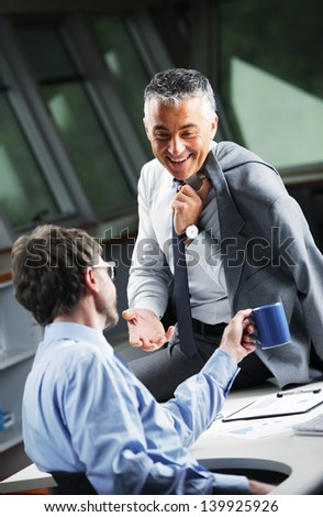 Mature Businessman consulting a partner at desk in office - stock photo