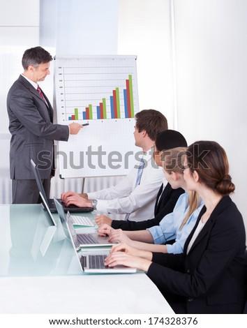 Mature Businessman Explaining Graph To His Colleagues - stock photo