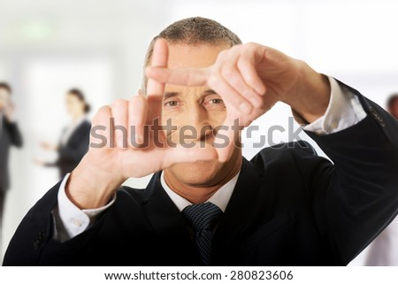 Mature businessman gesturing frame with hands. - stock photo
