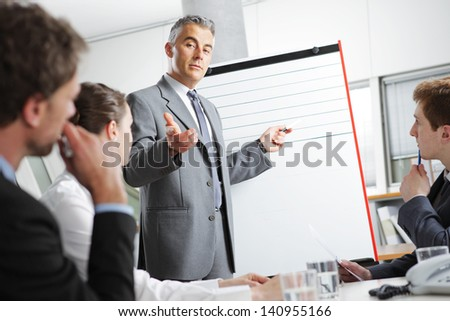 Mature businessman giving a presentation to his colleagues - stock photo
